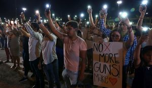 Demonstrators against gun violence carry No More Guns poster