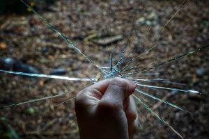 Photograph of fist breaking glass. Photo by Robert Anasch on Unsplash