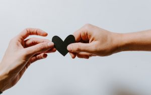 Hands holding a heart-shaped paper. Photo by Kelly Sikkema on Unsplash